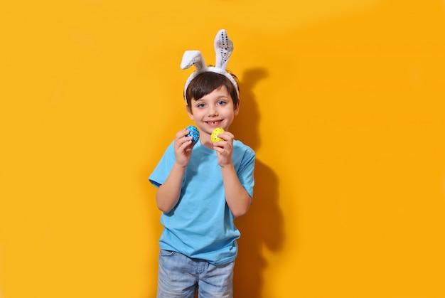 黄色の背景に着色された卵を保持しているイースターのウサギの小さな子供男の子を笑顔
