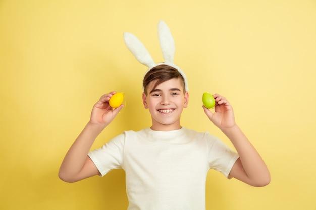 Улыбается. приближается охота за яйцами. кавказский мальчик как пасхальный кролик на желтом фоне студии. поздравления с пасхой. красивая мужская модель. понятие человеческих эмоций, выражения лица, праздников. copyspace.