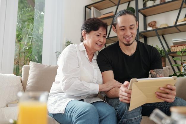 部屋のソファで母親と一緒にデジタルタブレットで何かを見ている長男笑顔