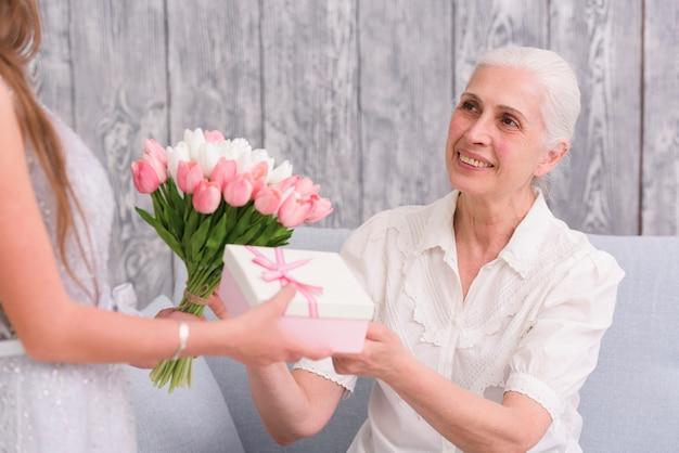 Улыбающаяся старшая женщина, получающая букет цветов и подарочную коробку, стоит перед своим внуком