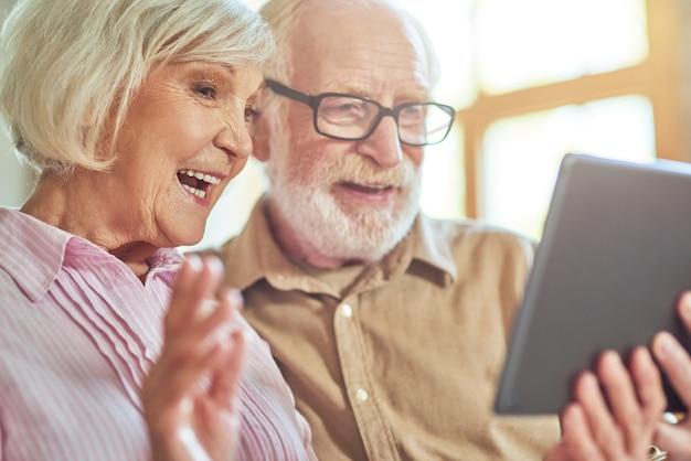 Smiling elder woman waving during video call near her husband