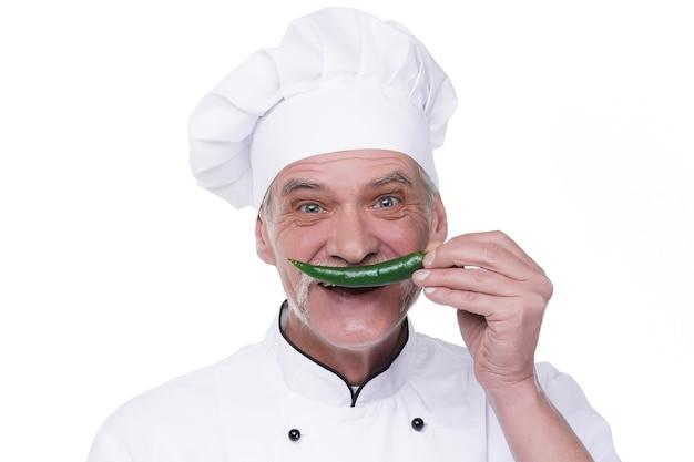 白い壁にピーマンと笑顔の年配のシェフ。野菜と幸せなシェフ