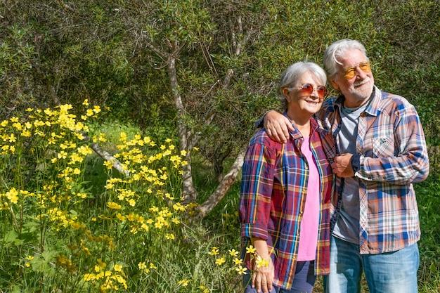 봄과 꽃을 즐기는 숲에서 웃는 노인 부부. 나무와 초원