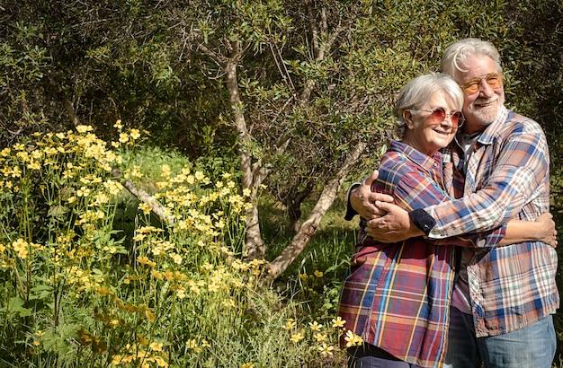 숲에서 웃고 있는 노부부는 봄과 꽃을 즐기며 서로 껴안고 있습니다. 건강한 삶을 사랑하는 두 은퇴자