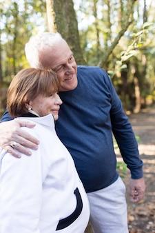 Улыбаясь пожилая пара позирует в парке