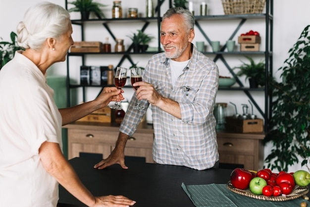 Smiling elderly couple toasting alcohol dinks in the kitchen