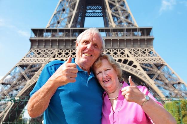 Sorridente coppia di anziani con la torre eiffel