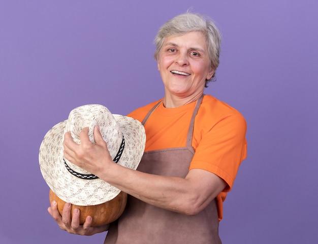 Sorridente giardiniere femminile anziano che tiene la zucca con il cappello da giardinaggio