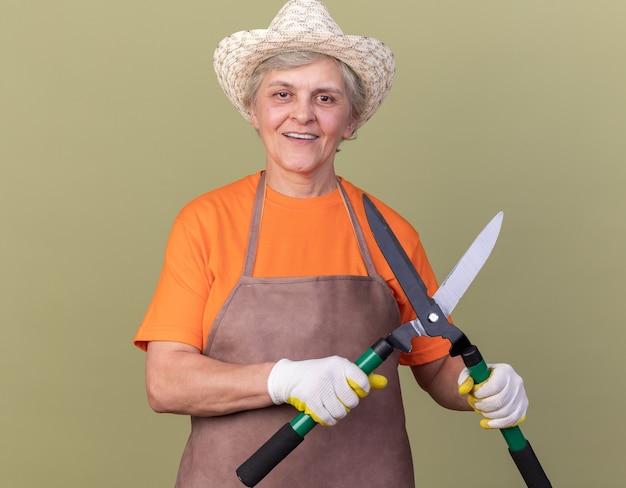 コピースペースとオリーブグリーンの壁に分離されたガーデニングはさみを保持しているガーデニングの帽子と手袋を身に着けている年配の女性の庭師の笑顔