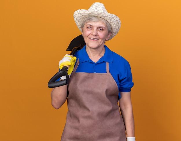 복사 공간이 있는 주황색 벽에 격리된 어깨에 삽을 들고 정원용 모자와 장갑을 끼고 웃고 있는 노년 여성 정원사