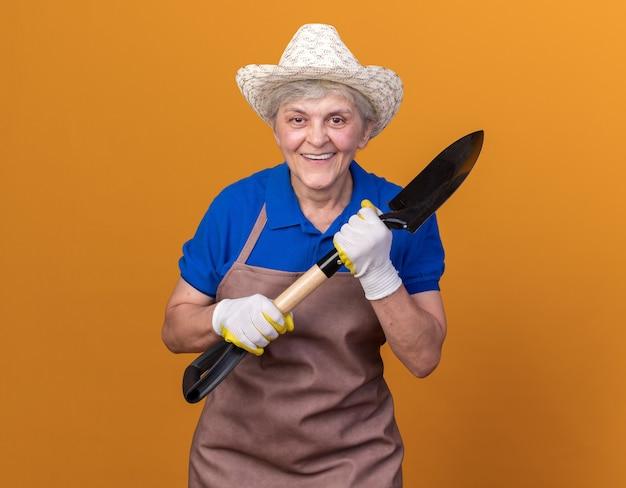 삽을 들고 원예 모자와 장갑을 끼고 노인 여성 정원사 미소