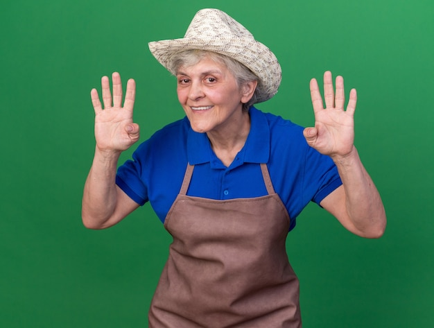 Smiling elderly female gardener wearing gardening hat gesturing four with fingers isolated on green wall with copy space