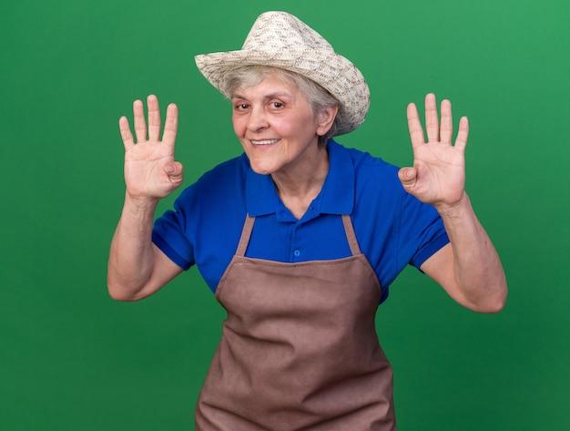 복사 공간 녹색 벽에 고립 된 손가락으로 4 몸짓 원예 모자를 쓰고 노인 여성 정원사 미소