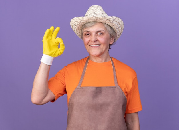 Smiling elderly female gardener wearing gardening hat and gloves gesturing ok sing isolated on purple wall with copy space