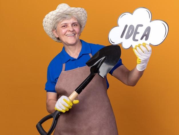 Sorridente giardiniere femminile anziano che indossa cappello e guanti da giardinaggio che tengono e puntano alla bolla delle idee con una vanga isolata sulla parete arancione con spazio di copia
