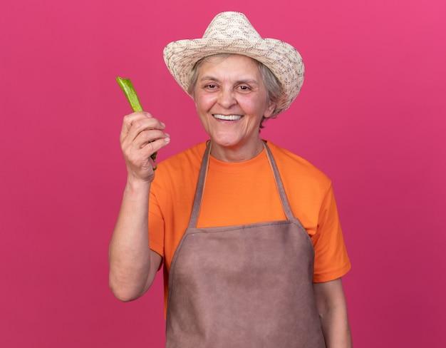 Sorridente giardiniere donna anziana che indossa cappello da giardinaggio tenendo peperoncino rotto