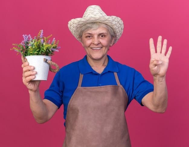 植木鉢を保持し、ピンクの指で4つを身振りで示すガーデニング帽子をかぶって笑顔の年配の女性庭師