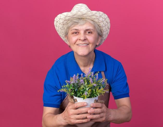 Sorridente giardiniere donna anziana che indossa cappello da giardinaggio che tiene vaso di fiori