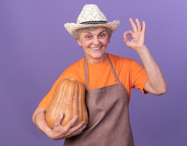 Sorridente giardiniere donna anziana che indossa cappello da giardinaggio tenendo la zucca e gesticolando segno ok
