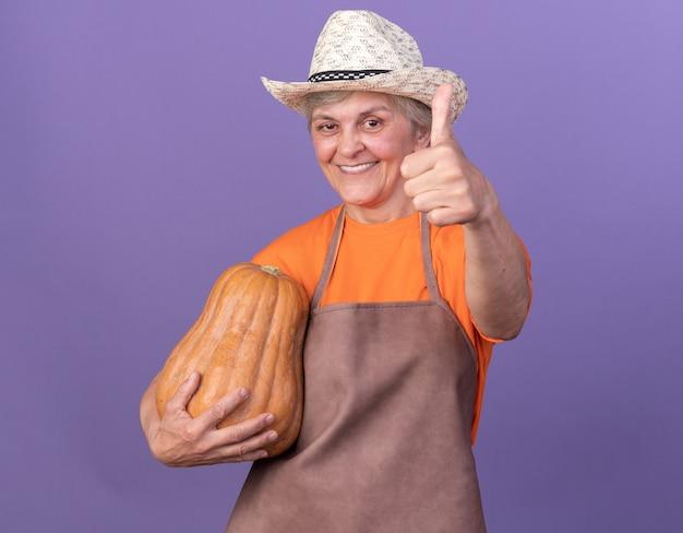 Sorridente giardiniere donna anziana che indossa cappello da giardinaggio tenendo la zucca e sfogliando