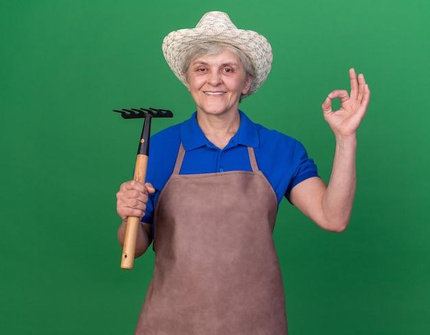 갈퀴를 들고 ok 사인을 몸짓으로 원예 모자를 쓰고 웃는 노인 여성 정원사