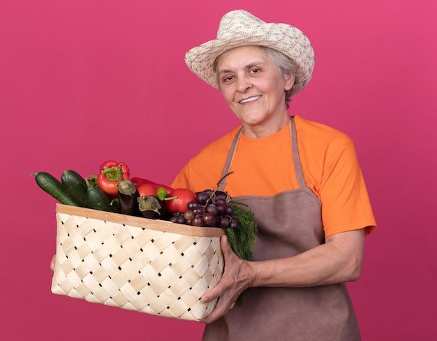 Sorridente giardiniere donna anziana che indossa cappello da giardinaggio che tiene cesto di verdure isolato su parete rosa con spazio copia