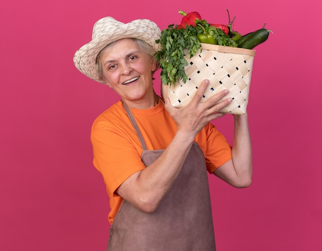 Улыбающаяся пожилая женщина-садовник в садовой шляпе держит корзину с овощами на плече