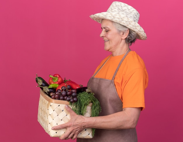 Sorridente giardiniere donna anziana che indossa un cappello da giardinaggio si erge lateralmente tenendo e guardando il cesto di verdure