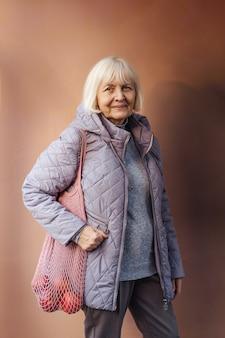 식료품과 면 자루를 들고 겉옷에 웃는 노인 여성.