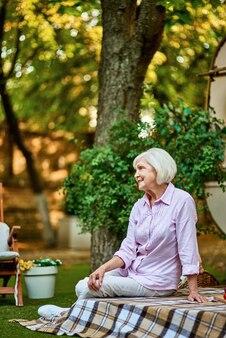 Улыбающаяся пожилая дама наслаждается отдыхом в саду