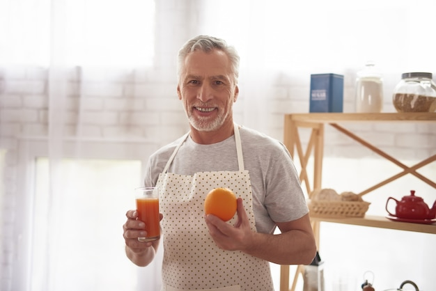 Smiling elderly man holds orange juice in kitchen.