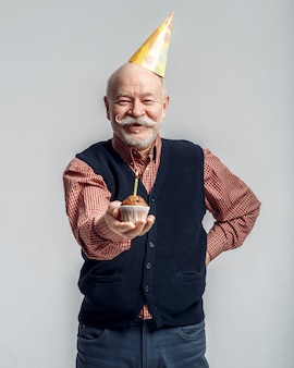 Smiling elderly man in party cap shows cake with candle, grey background. cheerful mature senior looking at camera in studio