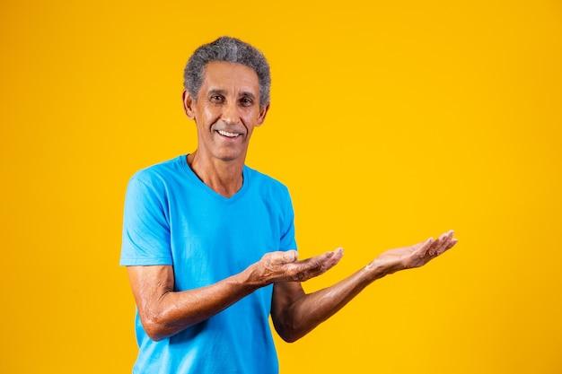 テキストのためのスペースで指さす笑顔の老人。