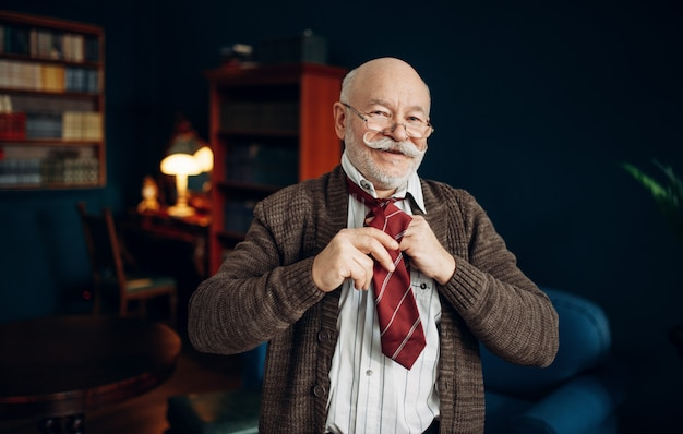Smiling elderly man puts on a tie in home office. bearded mature senior in living room, old age businessman