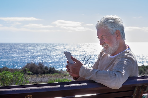 Smiling elderly man sitting on a bench in front to the sea, using technology with his smart phone. senior retiree relaxed enjoying retirement