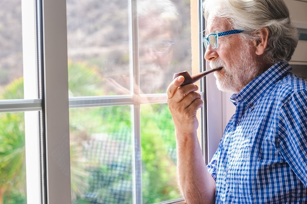 Smiling elderly man at the window looking out while smoking a pipe