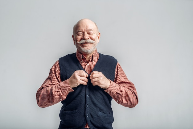 Smiling elderly man with mustache puts on a jacket on grey. cheerful mature senior looking at camera in studio