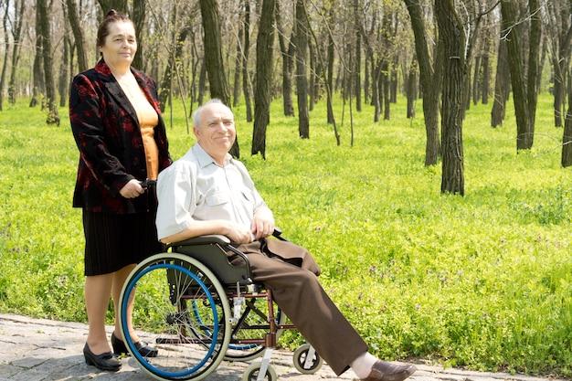 휠체어에 앉아 절단 된 한쪽 다리로 노인 미소 짓기