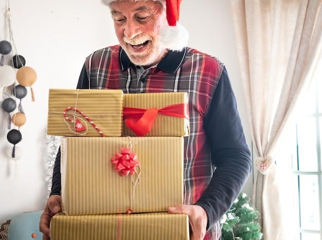 백그라운드에서 크리스마스 크리스마스 트리 선물을 들고 산타 모자와 함께 웃는 노인
