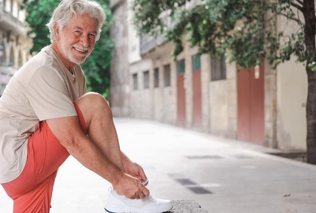 白い髪の笑顔の老人は、市内観光で彼の靴ひもを結びます。フィットネスとウォーキングを楽しんで引退したシニア