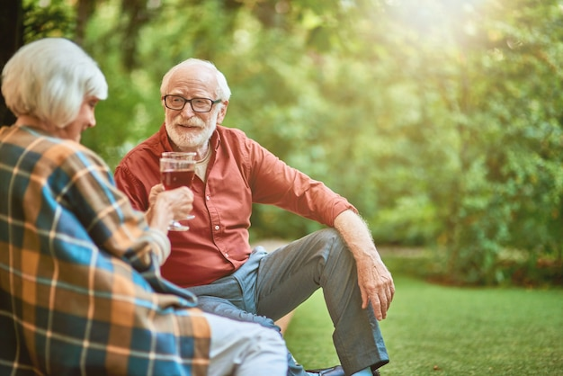 Smiling elderly spouses on a date in the garden
