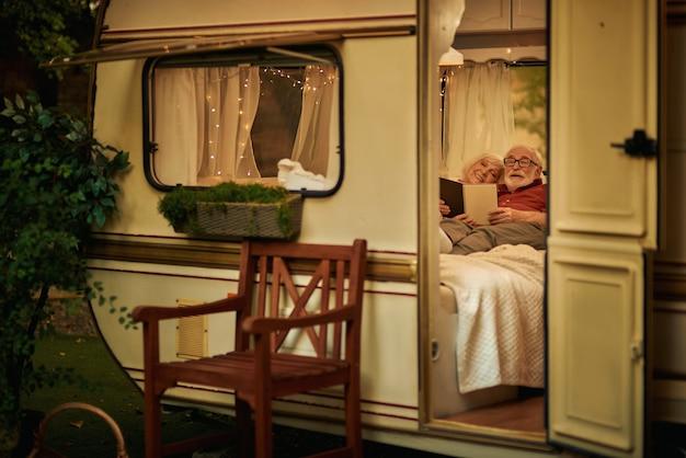 Smiling elderly spouses resting in their camper van