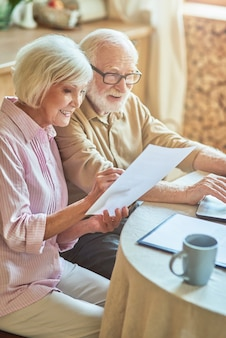 Smiling elderly woman checking bills with her spouse