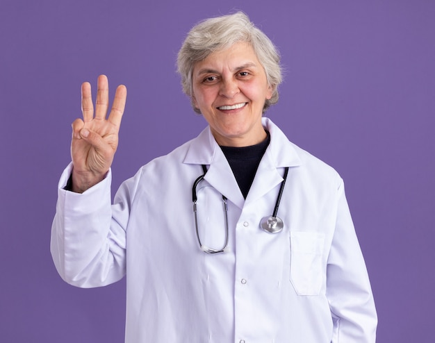 Smiling elderly woman in doctor uniform with stethoscope gesturing three with fingers
