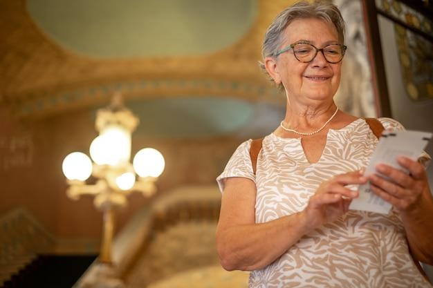 가이드를 바라보며 계단에 서서 바르셀로나에 있는 음악의 집에 들어가는 웃고 있는 할머니