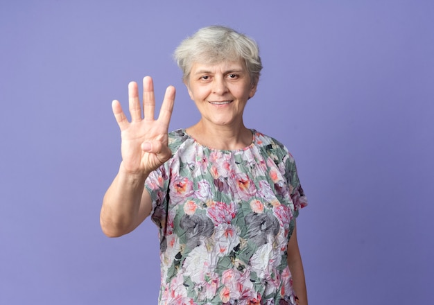 Smiling elderly woman gestures four with hand isolated on purple wall