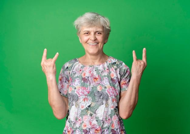 Улыбающаяся пожилая женщина жестикулирует рогами двумя руками, изолированными на зеленой стене
