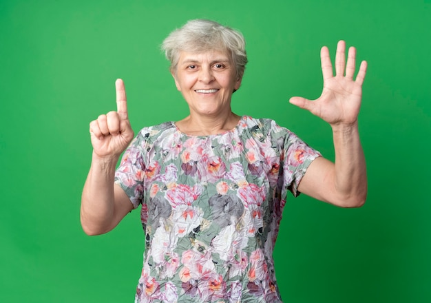Sorridente donna anziana gesti sei con le mani isolate sulla parete verde