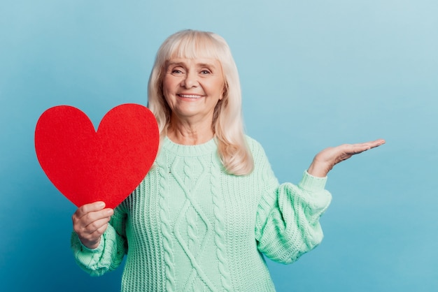 Smiling elderly woman hold hand advertise red heart card isolated on blue background