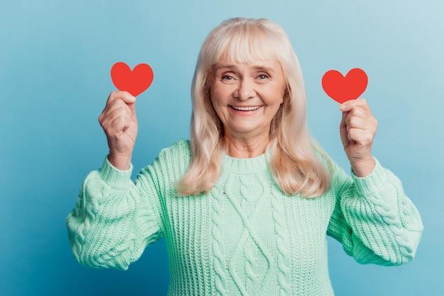 Улыбающаяся пожилая женщина держит маленькую красную сердечную карточку, изолированную на синем фоне